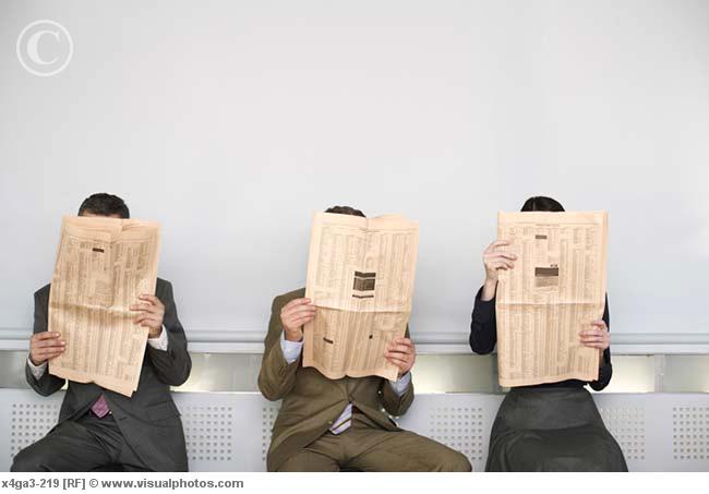 Three businesspeople reading newspaper. De www.visualphotos.com