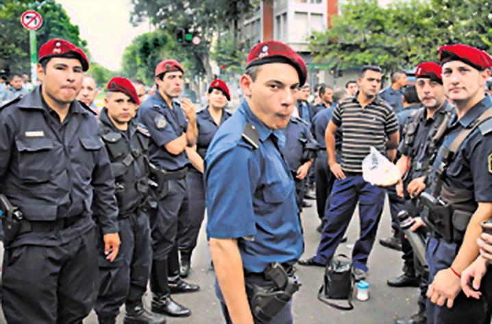 """Imagen de policías en """"huelga"""" el lunes 9 de diciembre 2013. Tapa diario """"Página12"""" de Buenos Aires, del martes 10."""