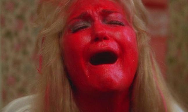 """Diane Ladd, gran actriz dramática, como la Madre Bruja, con la cara pintada con labial color sangre llora el """"abandono"""" de su hija (Laura Dern) por su apasionado amor por Nicolas Cage."""