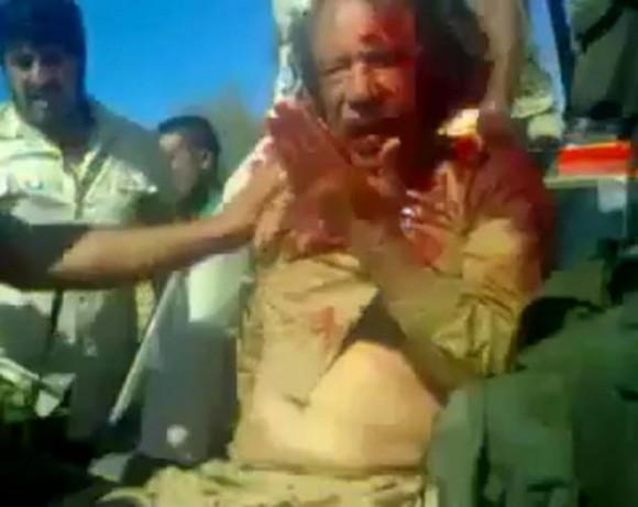 Gadaffi, líder de la ex república de Libia, linchado por mercenarios mientras vigilaban comandos ingleses.