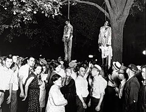 Linchamiento con horca en árbol público de afronorteamericano en Estados Unidos. 1930. Obsérvese al señor de camisa blanca de mangas cortas, casi en el medio, que señala orgulloso dónde debemos mirar y prestar atención.