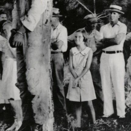 """Linchamiento de ciudadanos afronorteamericanos en USA. Horca pública sin juicio. Obsérvese el deleite de la niña, a la derecha, acompañada por su padre que la ha llevado al """"festejo público"""" ejemplarizador."""