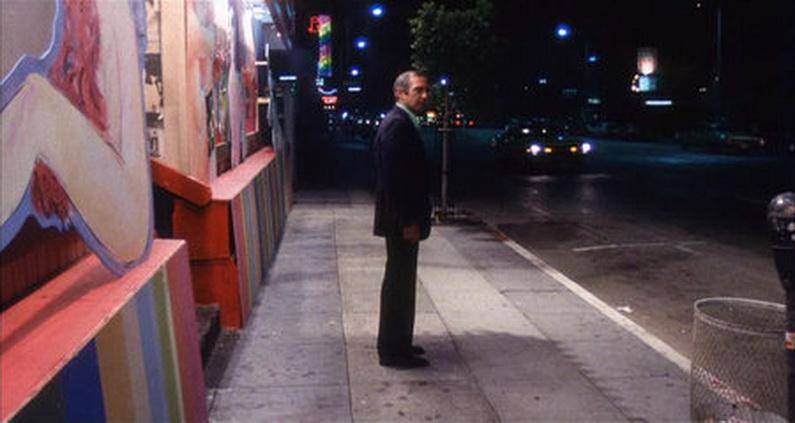 """Ben Gazzara, solo, solitario, abandonado, en la noche de la gran ciudad en """"El asesinato de un corredor de apuestas chino""""."""