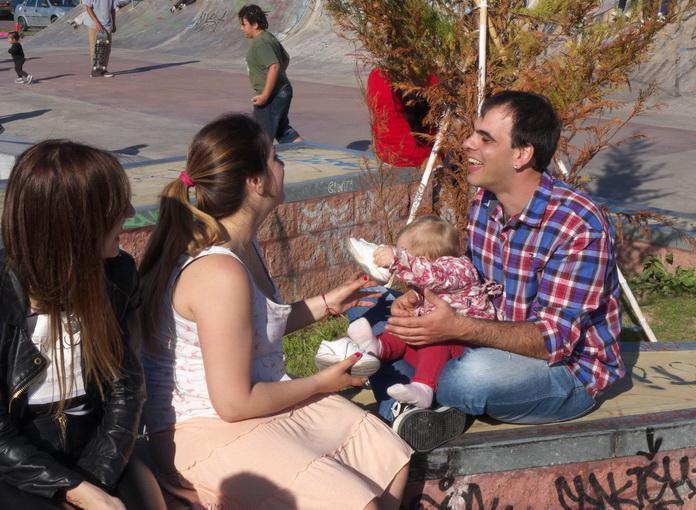 1. Bebé con cumbia y sol. Ella, la madre, acab de darle el pecho. Descubre su blanco seno y amamanta al niño. La cumbia está en toda la plata pista de skate. El padre feliz, chocho. A la izquierda, una chica en cuero negro, fetiche, mira. familiar, seguro. Amilcar Moretti, 29ç014, Argentina.