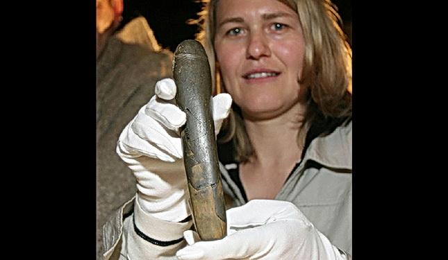 Una científica alemana sostiene en sus manos un Falo encontrado en ll mismo lugar que la Venus anterior, la cueva Hohle Fels, de hace 35 mil (35.000) años A. de C., Paleolítico Superior, Alemania.jpg