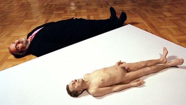 Ron Mueck al lado de una de sus esculturas hiperrrealistas  tamaño natural de muertos desnudos.