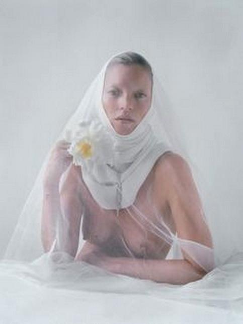 KATE MOSS fotografiada por Tim Walker en una especie de Juana de Arco monástica en su blancura y sexualidad con flor abierta.
