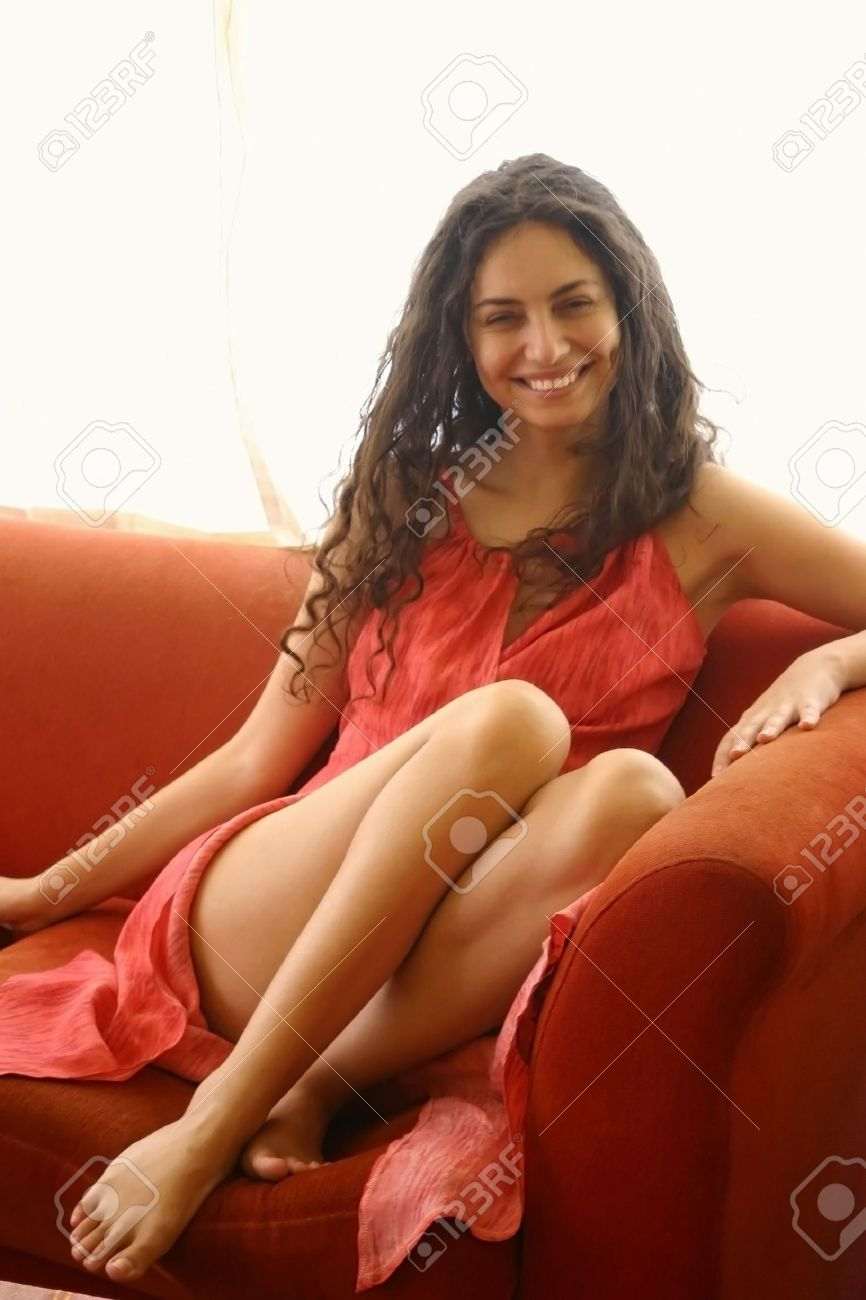 -mujer-en-vestido-rojo-sobre-un-sof-rojo--Foto-de-archivo